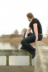 man sitting on a railing of a dock, looking out over the water.